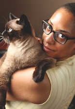 Sharlese Metcalf holding a Siamese cat.