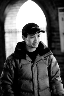 Black and white photo of Bao Tran in a winter jacket and baseball cap